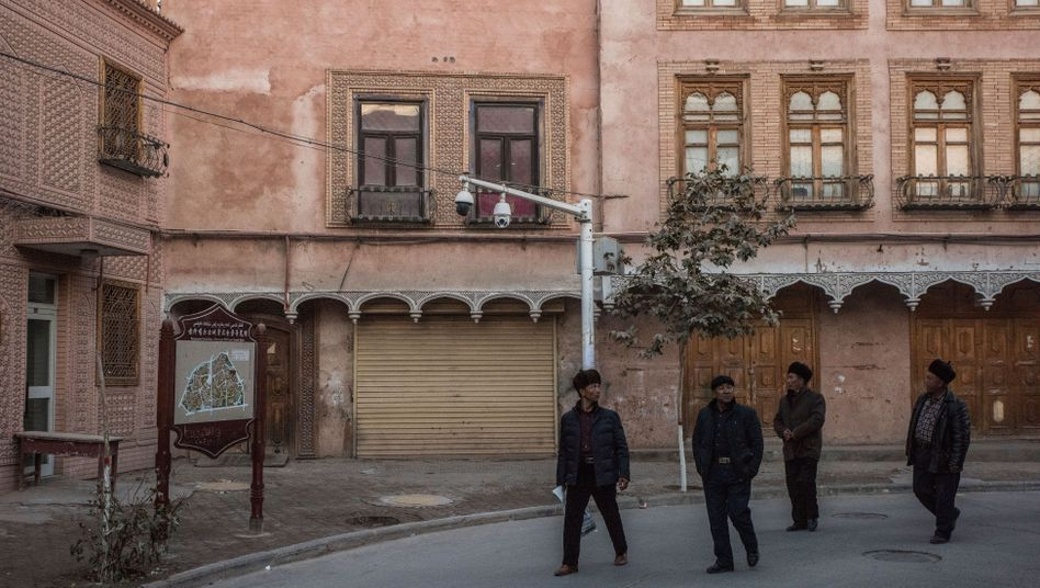 Men pass by surveillance cameras in Kashgar in the Xinjiang Uighur Autonomous Region.