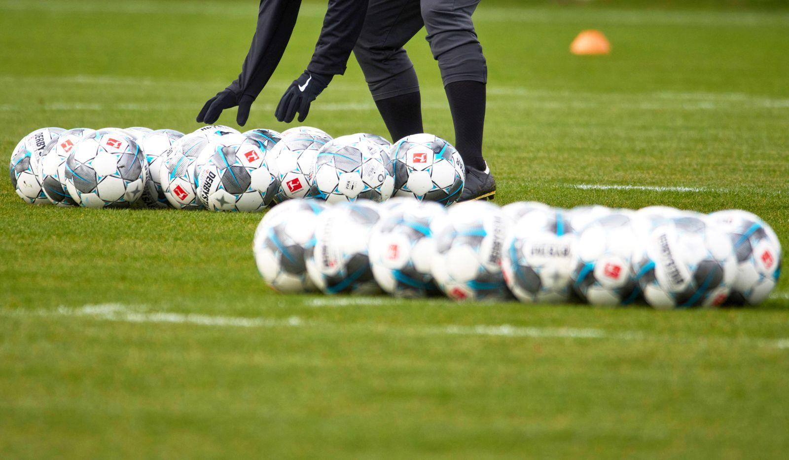 sehr viele Fu?b?lle liegen auf dem Trainingsplatz bereit, ein Trainer z?hlt nach, ob alle da sind. FC Augsburg, Training