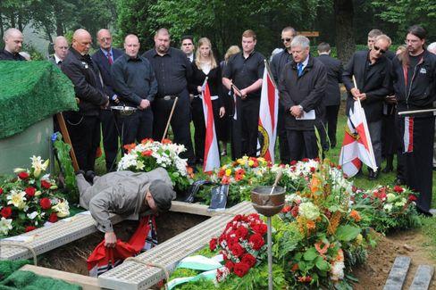 Hakenkreuzfahne für einen braunen Kameraden, vorn am Grab steht NPD-Chef Voigt: Trauerfeier für Friedhelm Busse