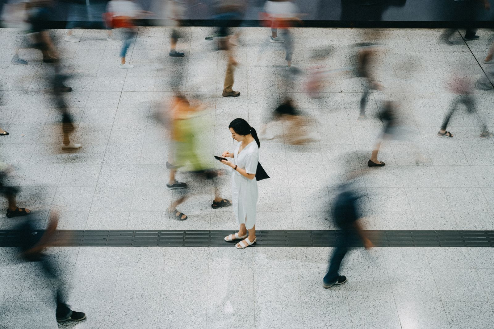 Young Asian woman using smartphone surrounded by commuters rushing by in subway station