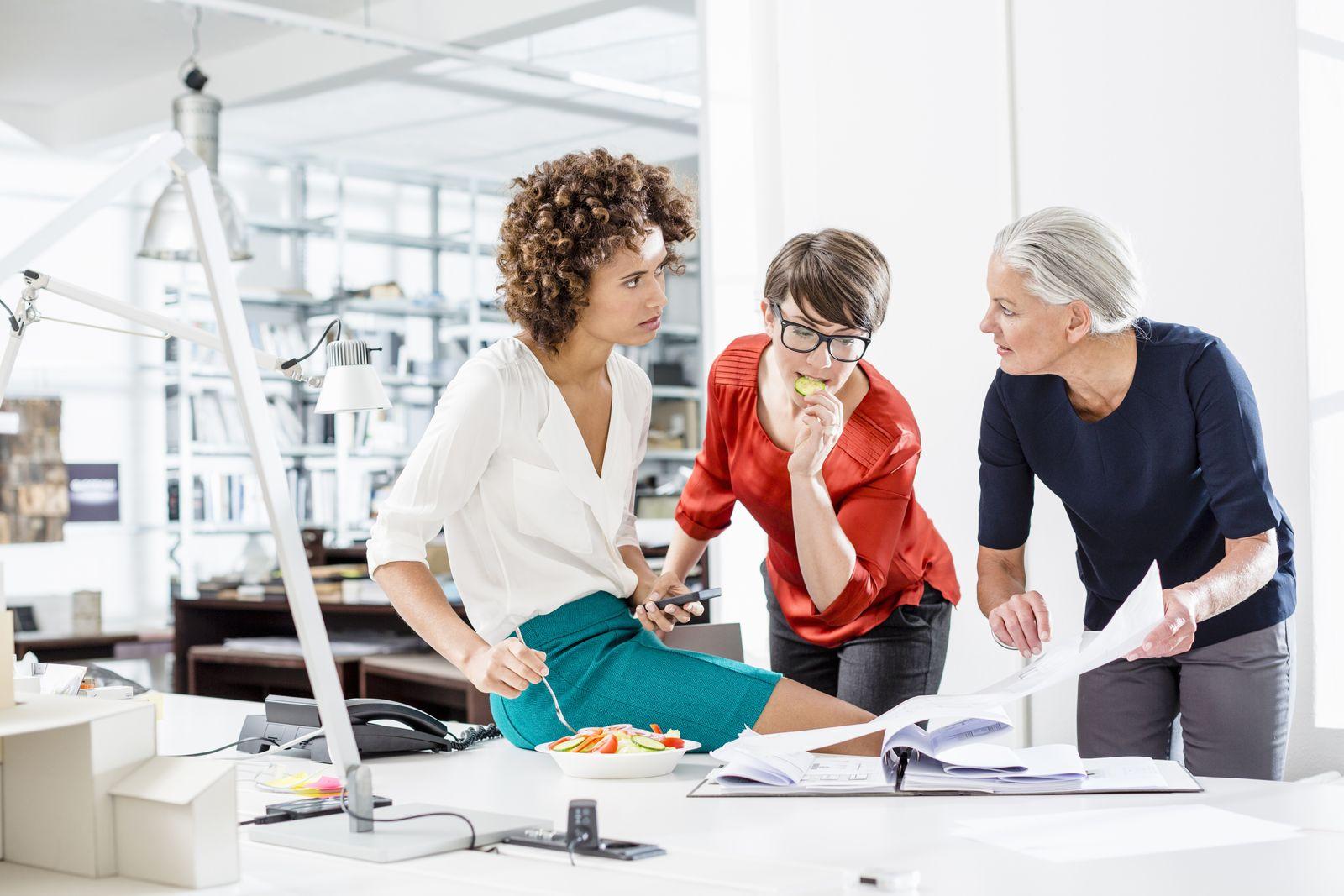 EINMALIGE VERWENDUNG Businesswomen eating and working