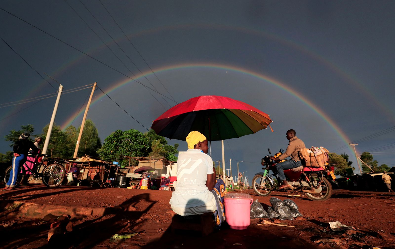 A double rainbow is seen above a woman holding an umbrella and selling snacks along the road in Siaya county