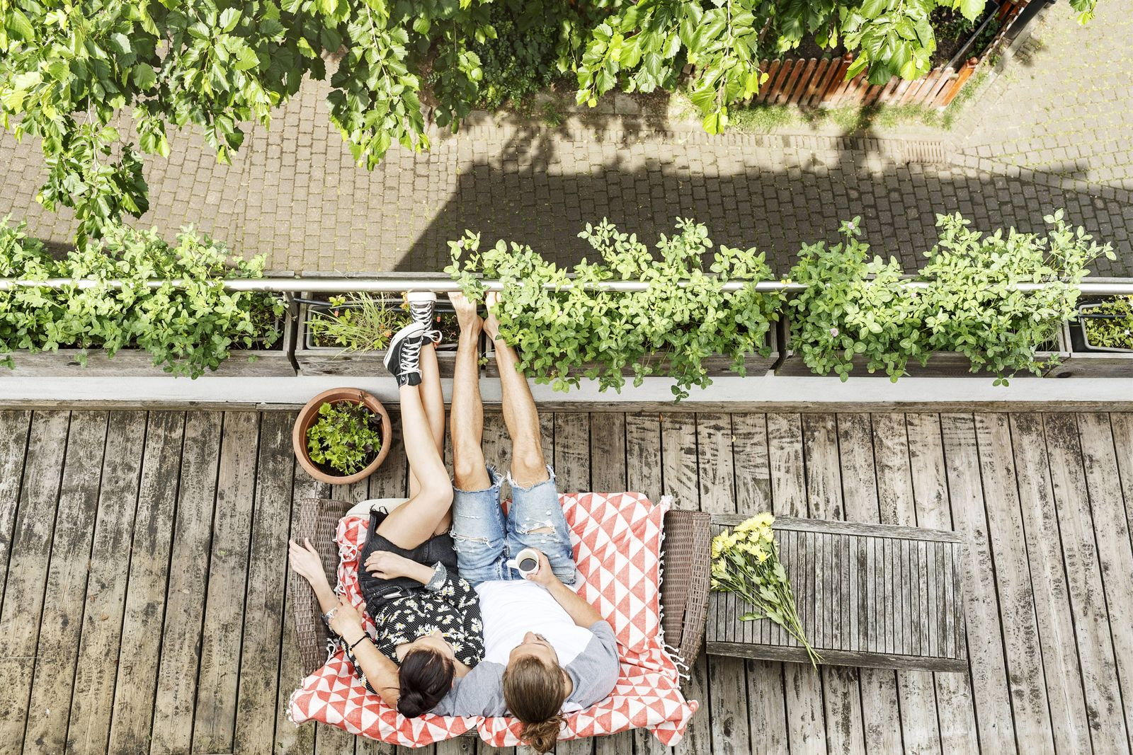 Young couple relaxing on their balcony in summer drinking coffee model released Symbolfoto property