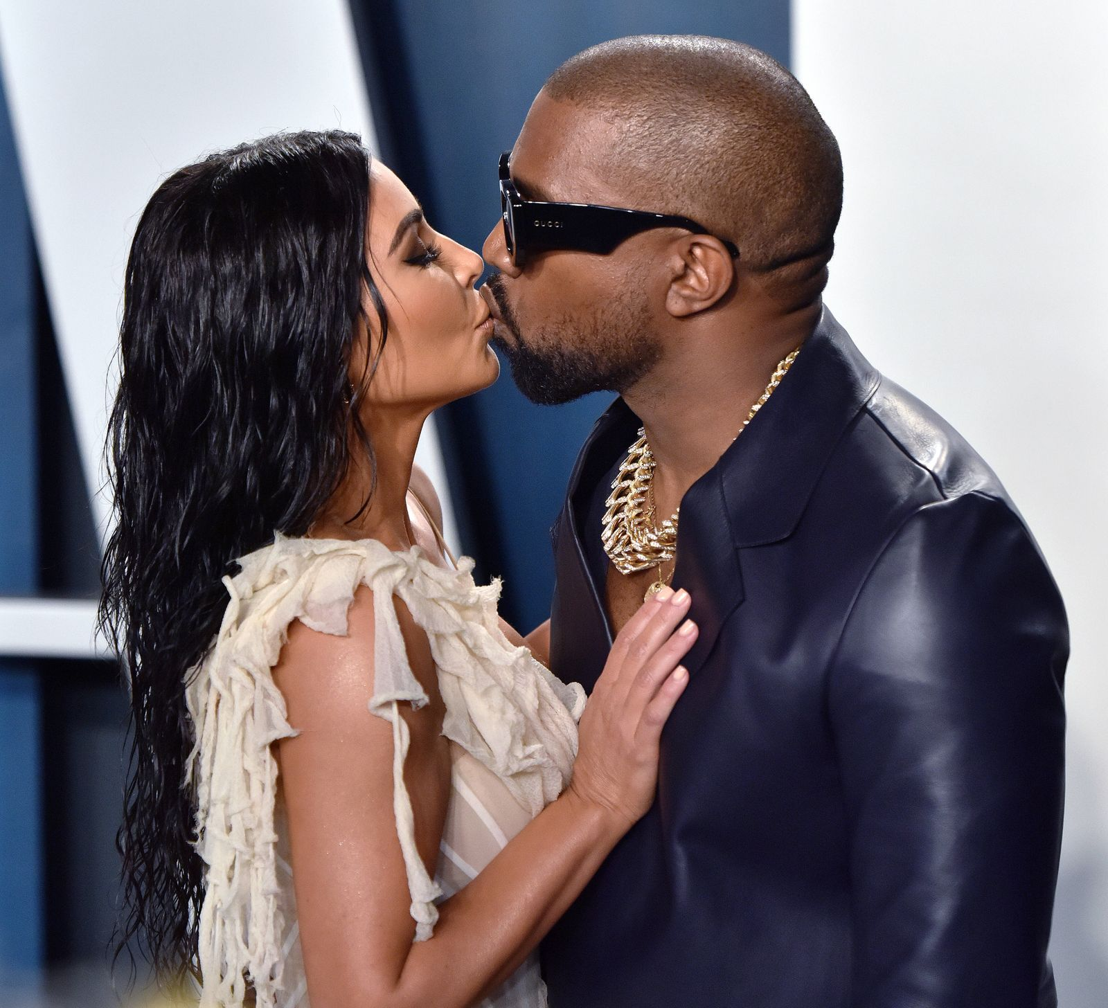 Kim Kardashian (L) and Kanye West kiss as they arrive for the Vanity Fair Oscar party at the Wallis Annenberg Center for