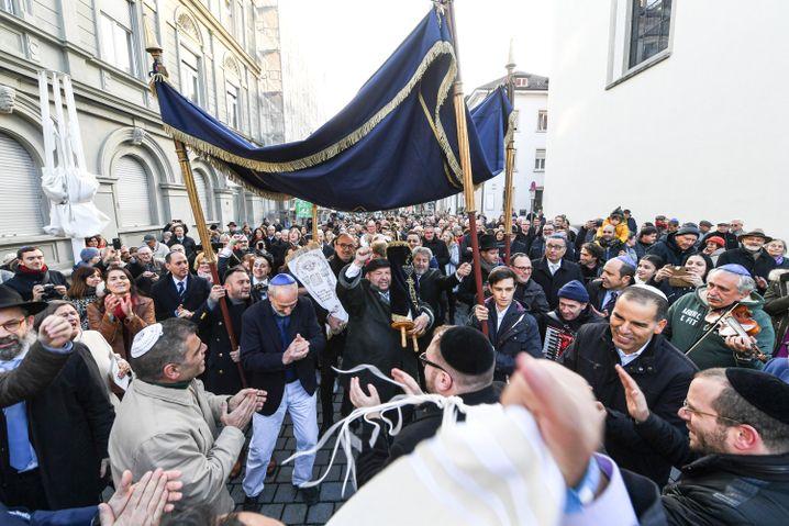 Mitglieder der jüdischen Gemeinde tragen Torarollen von der alten zur neuen Synagoge von Konstanz.