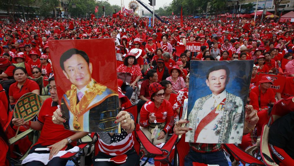 Anti-government ''red shirt'' protesters hold pictures of former Prime Minister Thaksin Shinawatra during a rally in Bangkok in April 2011.