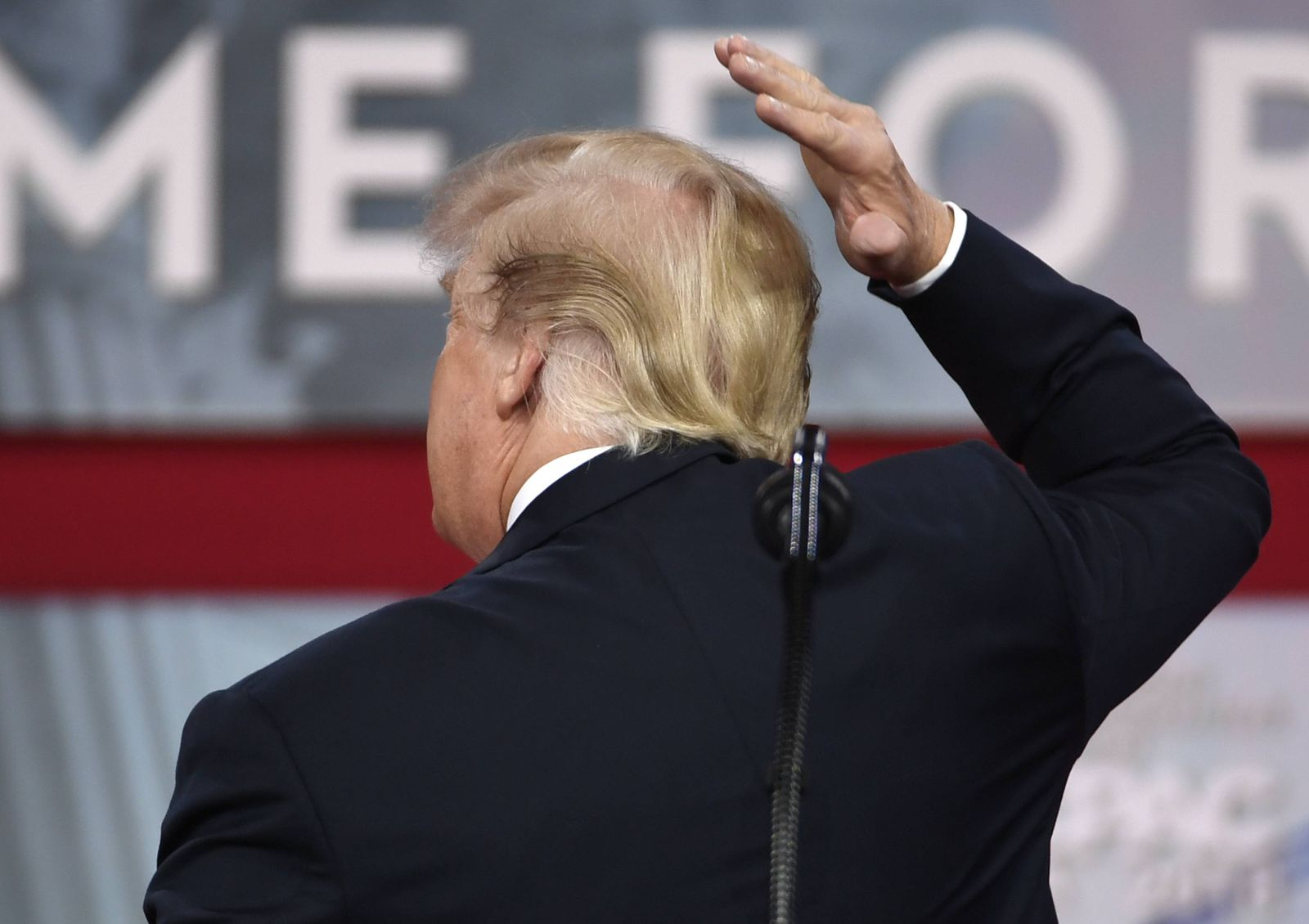 President Donald Trump playfully checks his hair after seeing it on a monitor prior to making remark