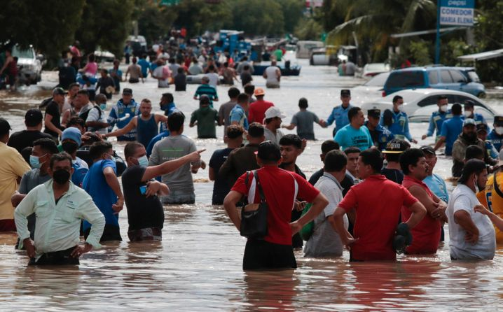 Menschen stehen in einem überschwemmten Gebiet in Honduras