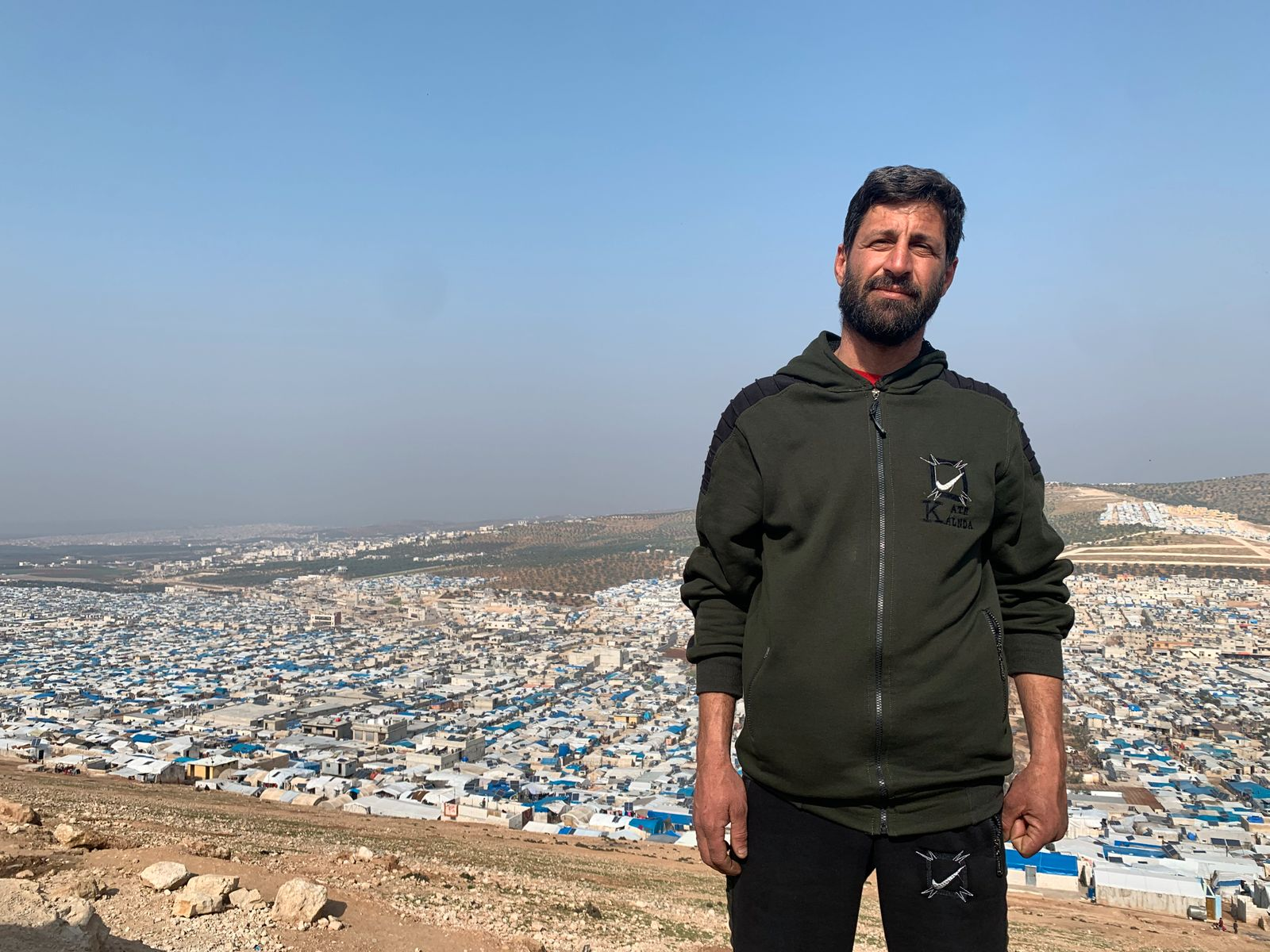 A resident of the huge improvised camp Atmeh seen behind him