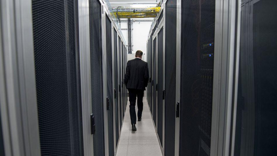 Ein Mitarbeiter der Firma De-Cix geht zwischen Server-Schränken hindurch.