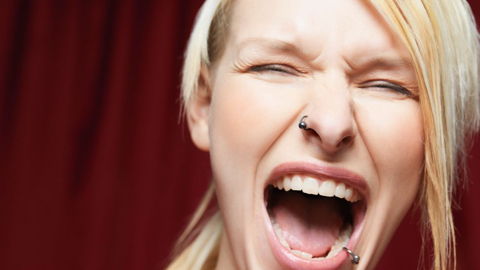 Junge Frau mit Nasen- und Lippenpiercing
