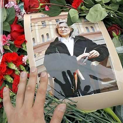 A visitor puts flowers at the portrait of prominent Russian journalist Anna Politkovskaya at the site of her murder.