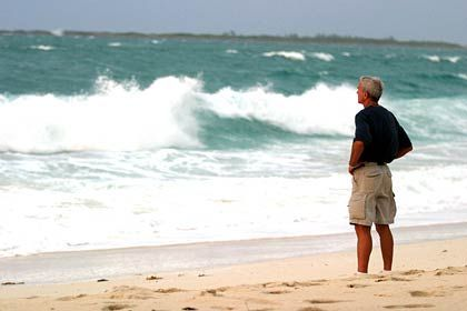 Steve Mannhard, of Summerdale, Ala., stands on the Paradise Island beach off the Atlantis Resort in the Bahamas watching the heavy surf pound the beach Thursday, Sept. 2, 2004. Wind gusts picked up along the North coast of New Providence as Hurricane Frances continues its path through the central Bahama Islands