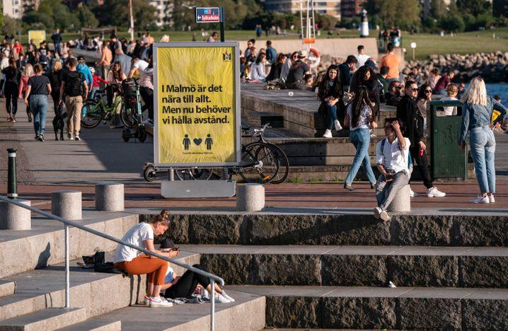 Malmö (Schweden): Menschen genießen das warme Abendwetter hinter einem Schild, das auf die Abstandsregeln hinweist