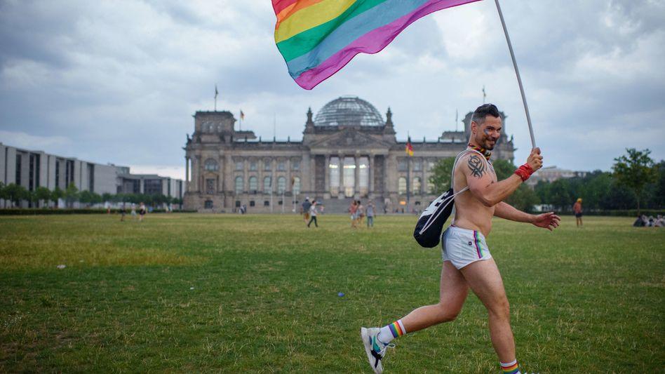 Ein Teilnehmer des CSD mit Regenbogenflagge vor dem Bundestag