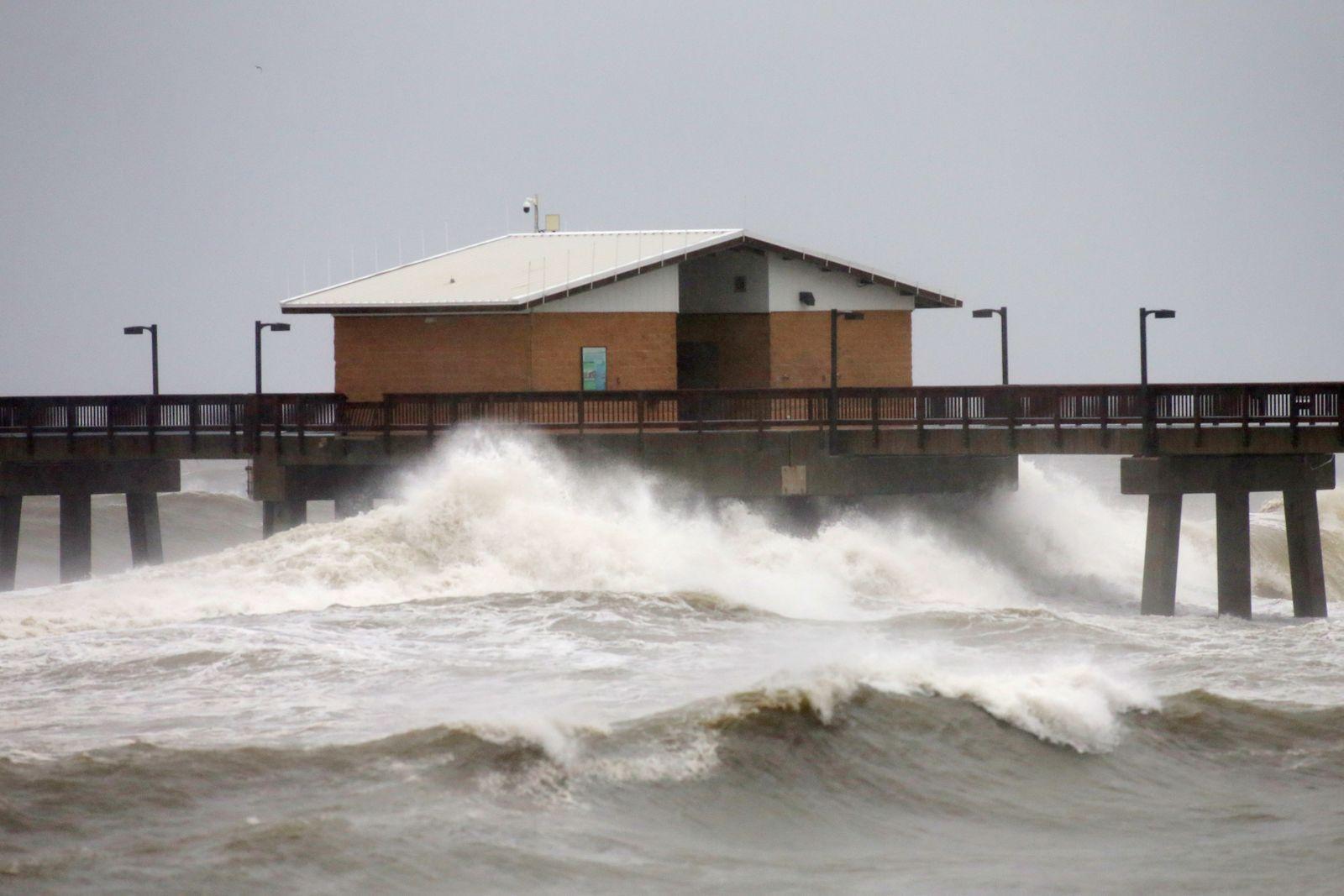 Waves crash along a pier as Hurricane Sally approaches in Gulf Shores