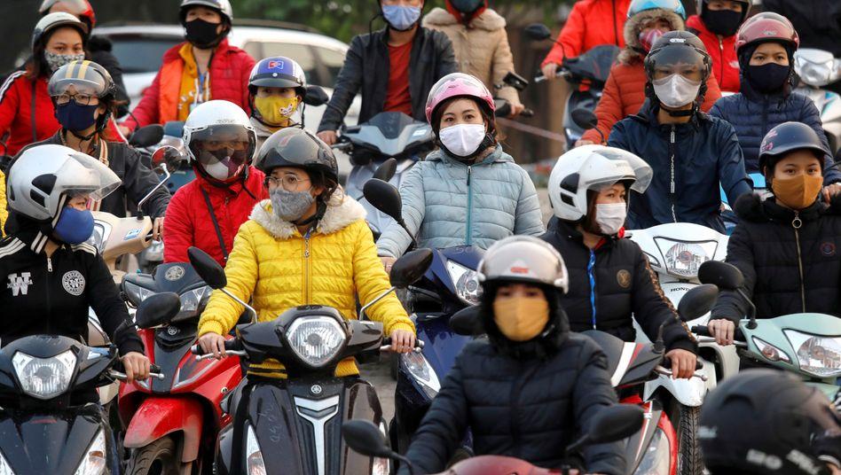 Rollerfahrer mit Atemschutz in der vietnamesischen Provinz Hai Duong: Social Distancing ist im Feierabendverkehr kaum möglich