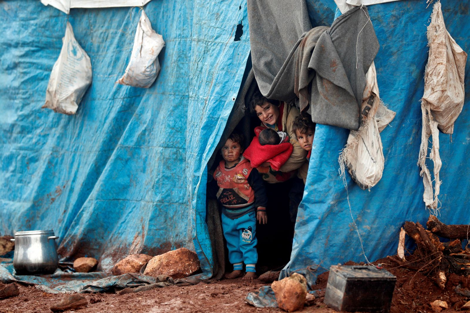 Displaced Syrian children look out from their tents at Kelbit refugee camp in Idlib province