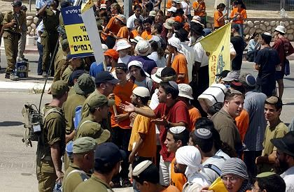 Israeli anti-pullout protestors argue with Israeli soldiers.