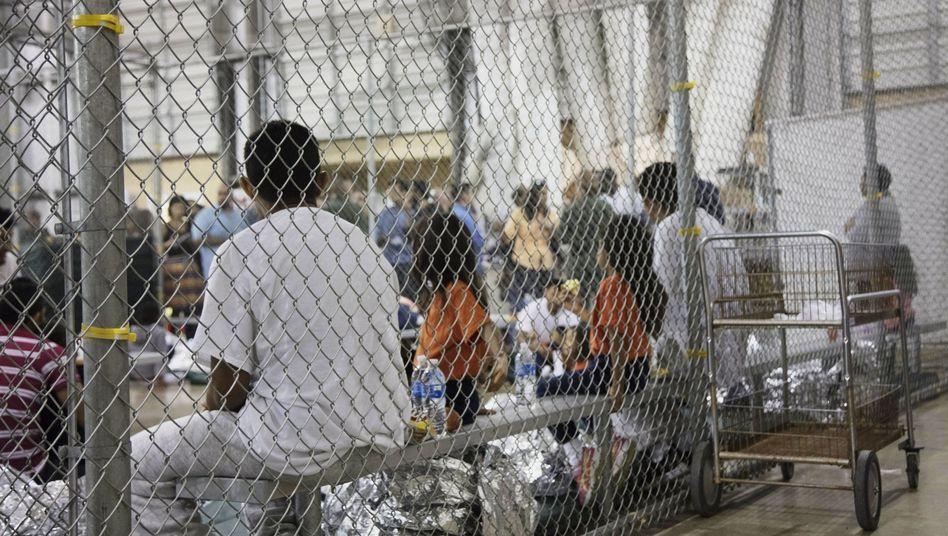 In Texas sitzen Menschen, die im Zusammenhang mit illegalen Grenzübertritten in Gewahrsam genommen wurden, in einem Käfig.