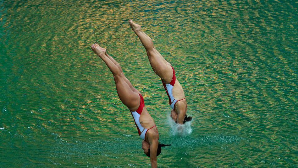 Synchronspringen der Frauen am grünen Pool