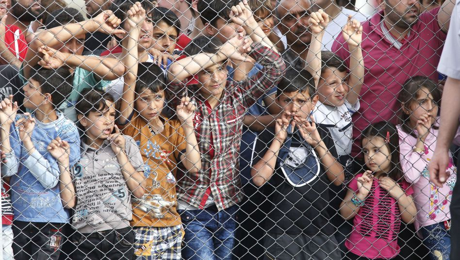 Migrants standing behind a fence at a refugee camp in southeastern Turkey.