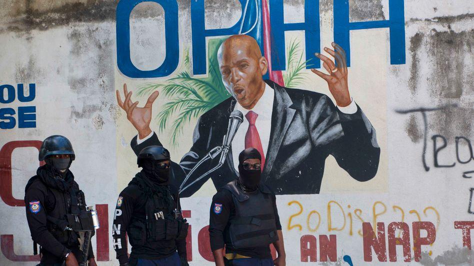 Polizisten in Port-au-Prince vor einem Graffiti, das Jovenel Moïse zeigt