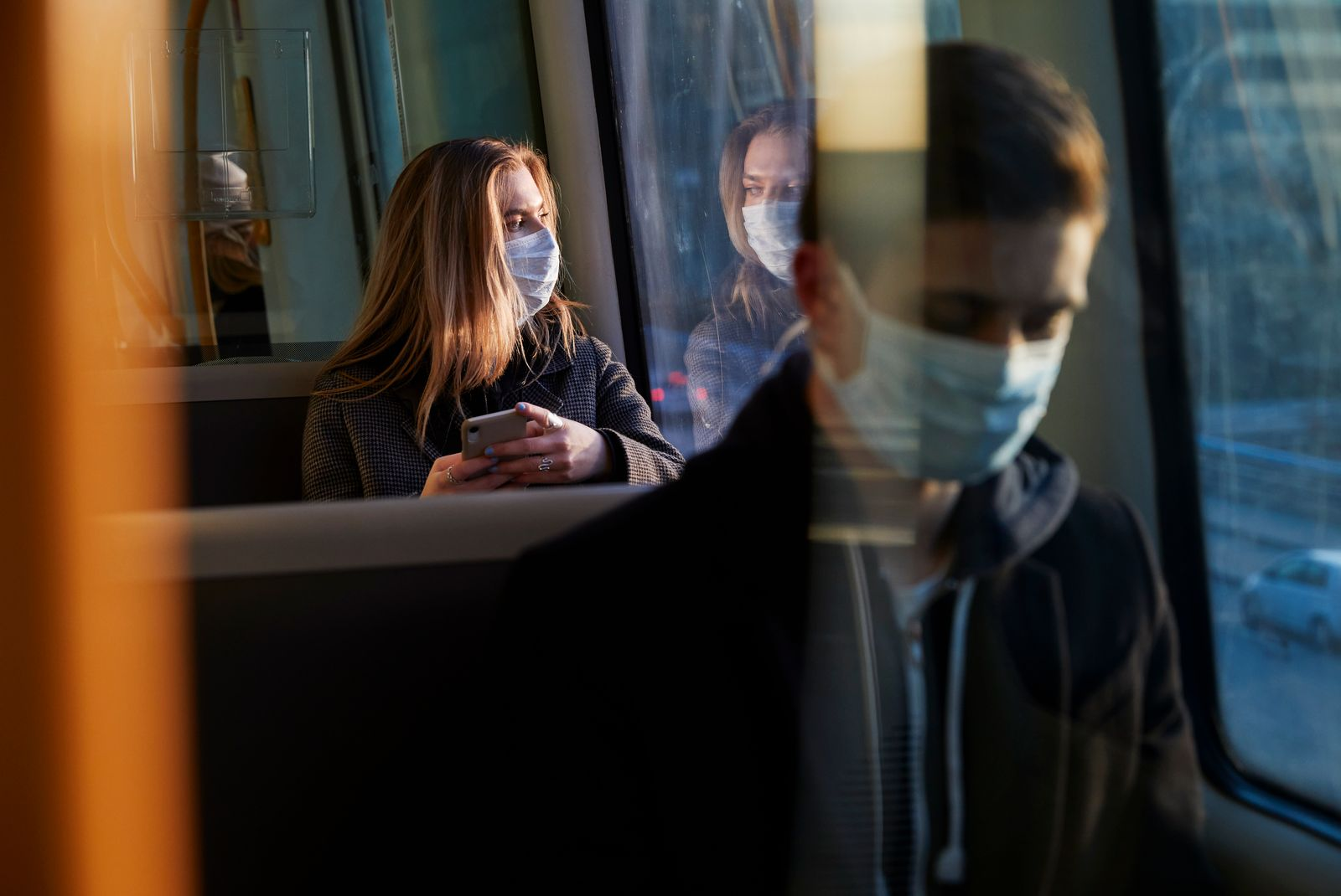 young woman sitting in train wearing protective mask, using smartphone