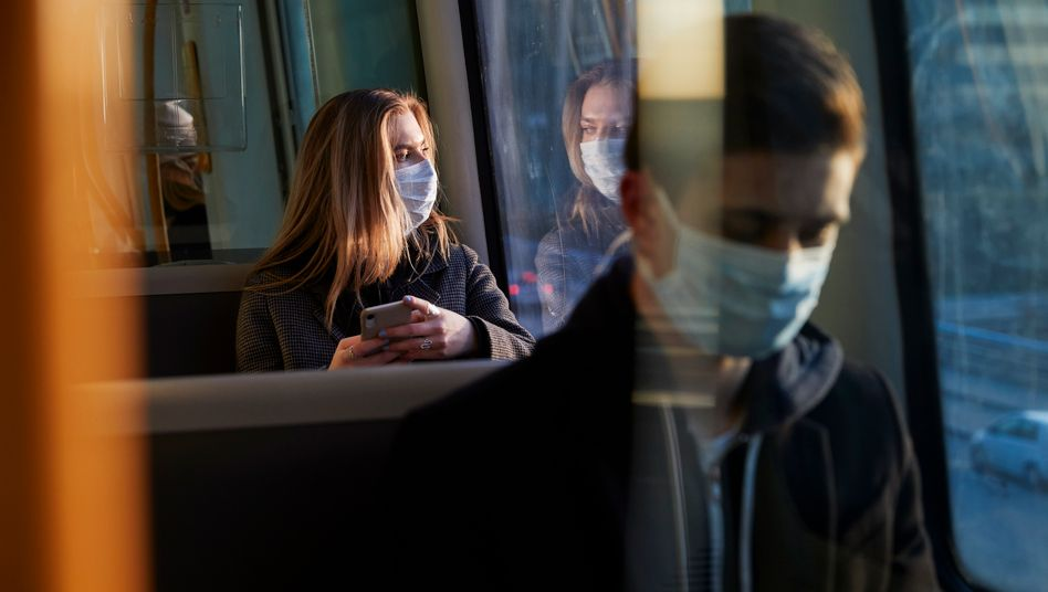 Menschen mit Mund-Nasen-Schutz sitzen in einem Zug
