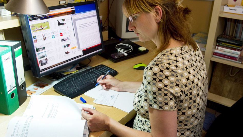 Eine Frau sitzt im Arbeitszimmer (Symbolbild)