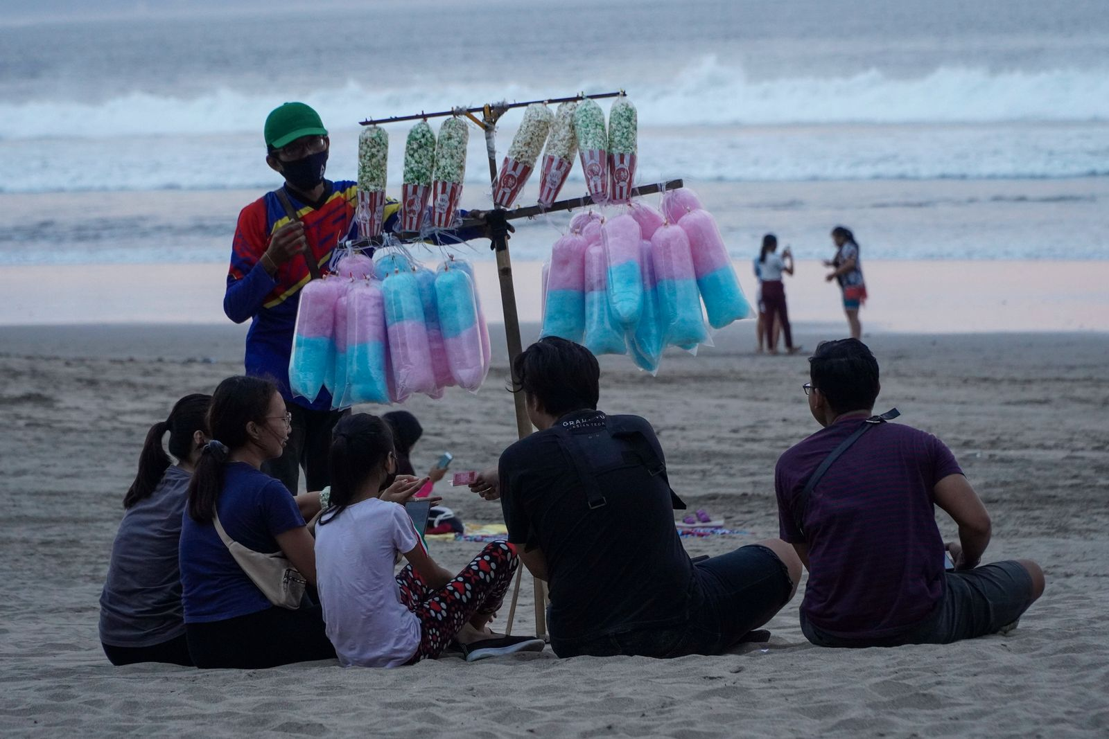 August 10, 2020, Badung, Bali, Indonesia: A street vendor man peddle his product among the tourists. People enjoy their