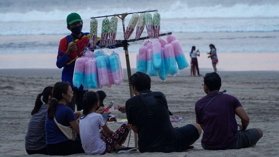 Ein Strandverkäufer bietet Gästen auf Bali Süßigkeiten an: Internationale Touristen müssen noch draußen bleiben