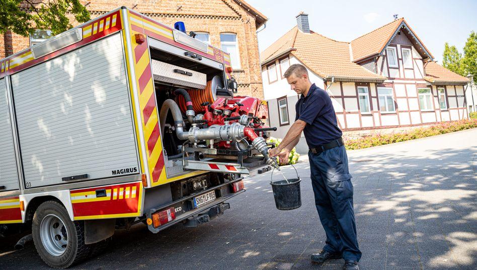 Ein Feuerwehrmann in Lauenau zapft Wasser an einem Löschfahrzeug