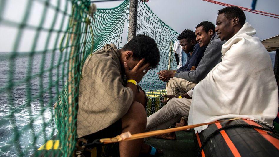 Geflüchtete sitzen an Bord eines Rettungsbootes.