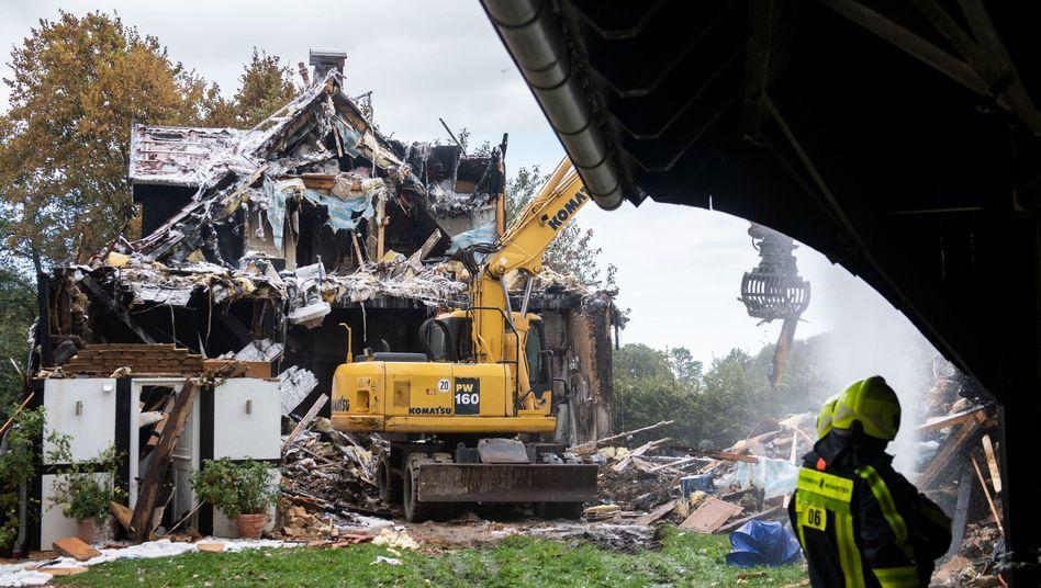 Ein Bagger reißt nach einem Brand in Münster ein Fachwerkhaus ab