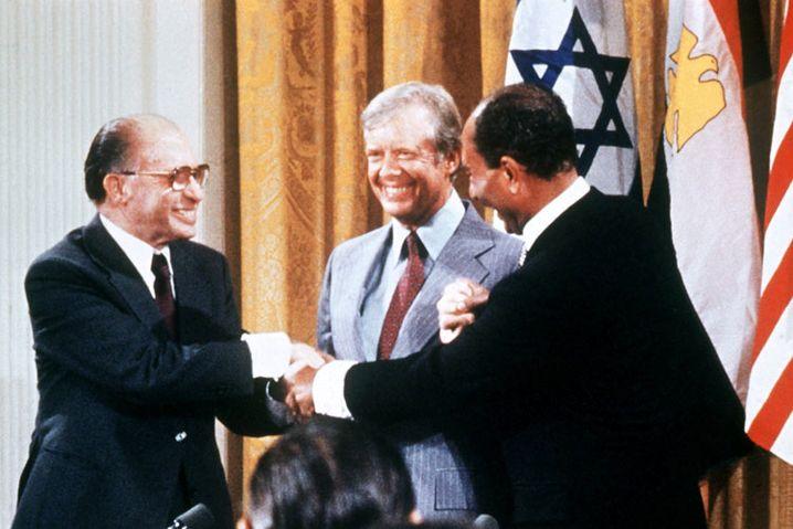 Historischer Händedruck: Am 17. September 1978 besiegelten der israelische Ministerpräsident Menachem Begin (li.) und der ägyptische Präsident Anwar al-Sadat das Friedensabkommen von Camp David. In der Mitte US-Präsident Jimmy Carter