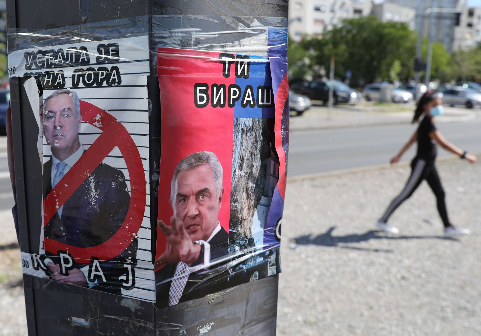 A woman walks near an anti Montenegro President Milo Djukanovic poster ahead of Montenegrin Assembly election in Podgorica