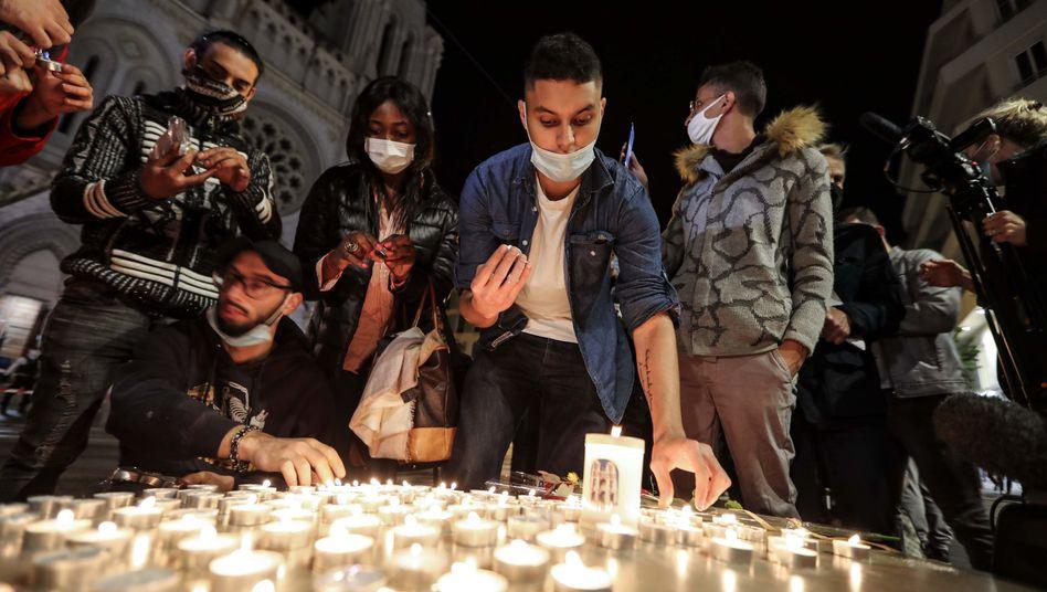 Menschen gedenken vor der Kirche Notre Dame in Nizza der Opfer eines islamistischen Attentäters