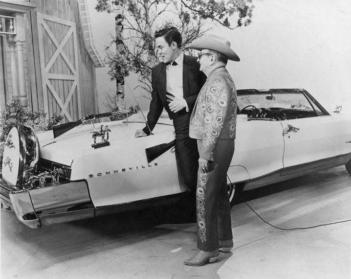 Nudie Cohn mit dem Schauspieler und Countrysänger Jimmy Dean vor einem gepimpten Pontiac Bonneville