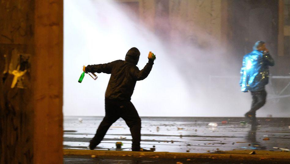 Ein Mann wirft in Leipzig eine Flasche in Richtung eines Wasserwerfers der Polizei.