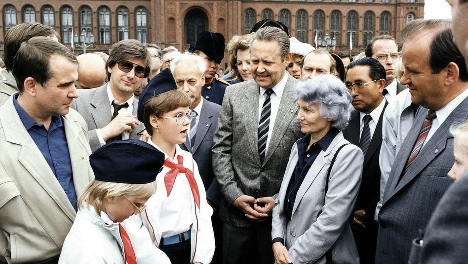 Altvordere agitieren die Jugend: Volksbildungsministerin Margot Honecker, SEDPolitbüromitglied Günter Schabowski (M.) und der Chef der FDJ Eberhard Aurich (l.) treffen »Thälmann-Pioniere« vor dem Roten Rathaus in Ostberlin, Mai 1987.
