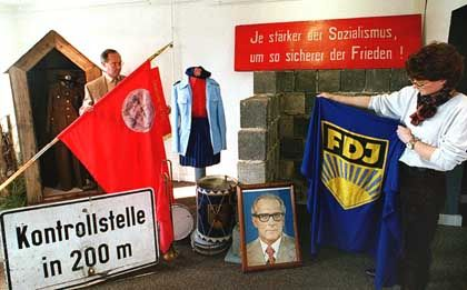 An employee of an East Germany-themed museum in Eichsfeld shows off an FDJ flag. The organization is back, 18 years after the fall of the Wall.