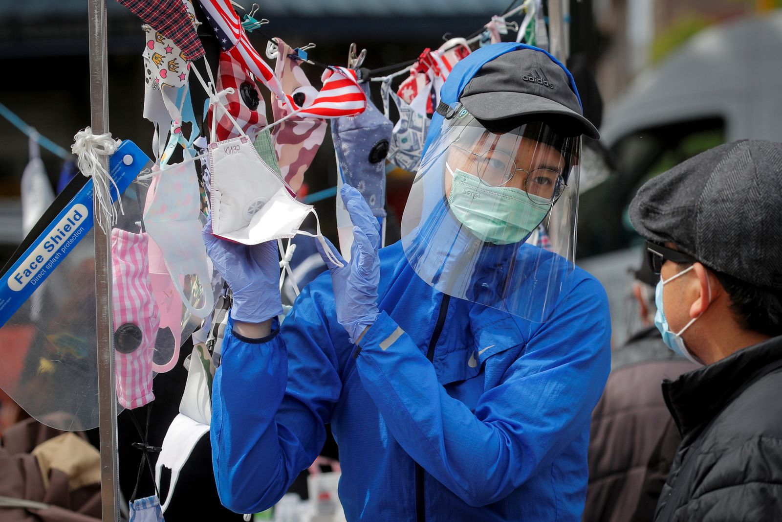 A man speaks to a street vendor about face masks, during the outbreak of the coronavirus disease (COVID-19), in the Corona section of Queens, New York