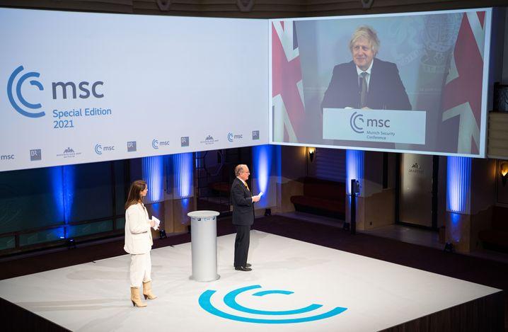 Konferenzteilnehmer Boris Johnson mit Moderator Wolfgang Ischinger und Moderatorin Natalie Amiri