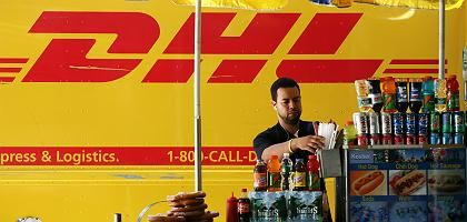 A DHL delivery truck is parked next to a hot dog stand in New York: Mass job cuts are expected at Deutsche Post's US subsidiary.