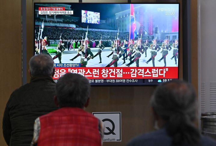 Menschen im südkoreanischen Seoul verfolgen auf einem Fernseher in einem Bahnhof die Parade zum 75. Gründungstag der herrschenden Arbeiterpartei in Nordkorea