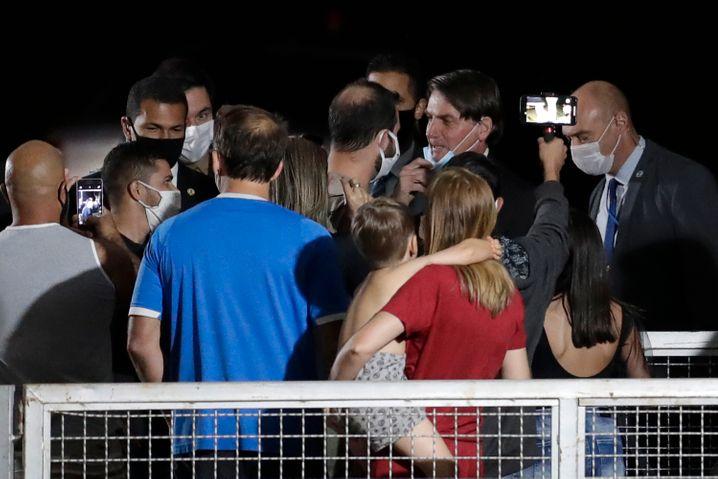 Jair Bolsonaro (mit Maske am Kinn) am Montag inmitten seiner Anhänger