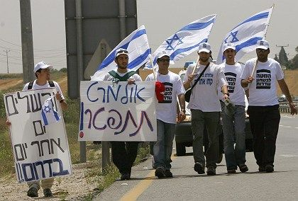 Israeli protesters marching to Tel Aviv carry flags and a placard reading 'Olmert Resign.' Prime Minister Ehud Olmert is coming under increasing pressure to step down after a report damned his conduct of the Lebanon war.