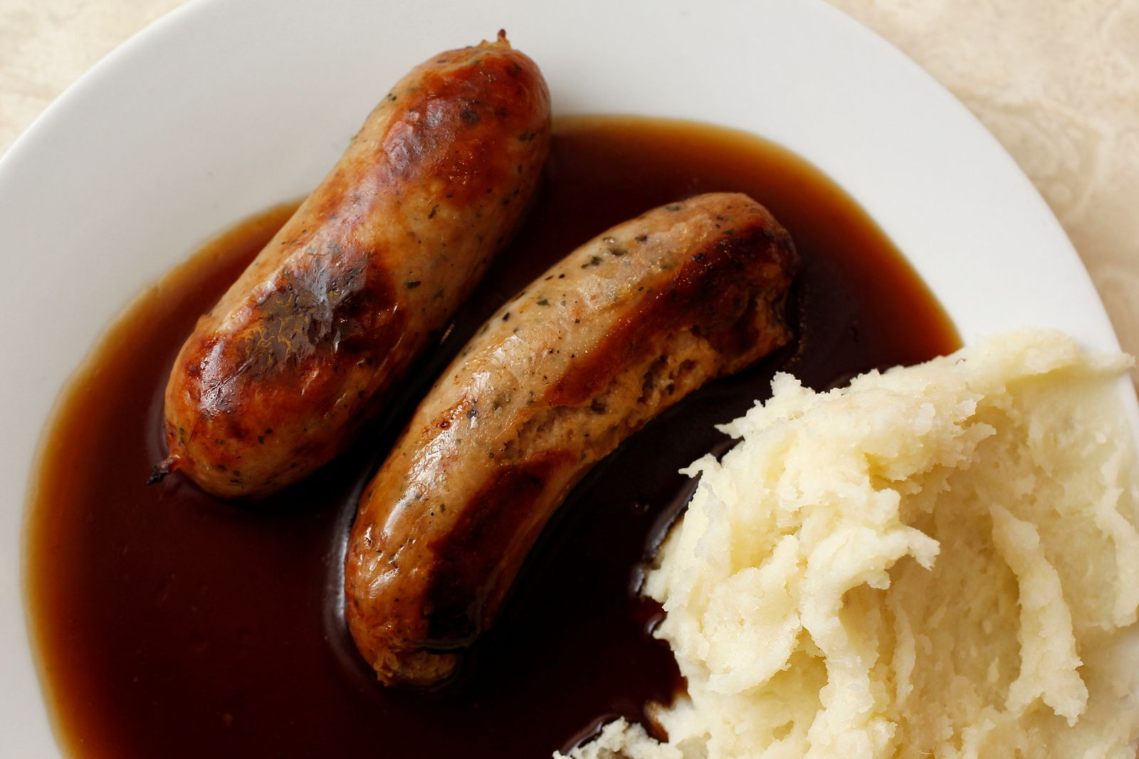FILE PHOTO: A traditional British meal of sausages and mashed potato in gravy, known as Bangers and Mash, is pictured in G. Kelly's pie and mash shop in east London