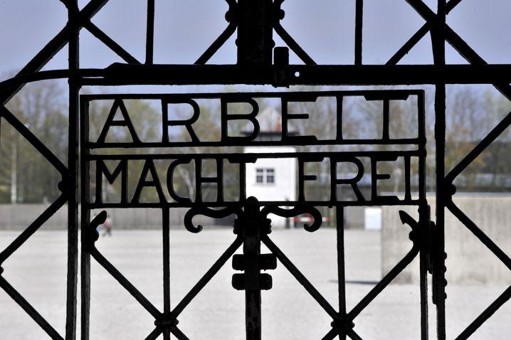 ARCHIV - Das stählerne Eingangstor mit der Inschrift «Arbeit macht frei» im ehemaligen Konzentrationslager in Dachau bei München (Bayern), aufgenommen am 18.04.2008. Das KZ Dachau gehörte zu den ersten von den nationalsozialistischen Machthabern in Deutschland eingerichteten Konzentrationslagern. Dort wurden bereits am 22. März 1933, wenige Wochen nach der Machtergreifung Hitlers, die ersten Häftlinge eingesperrt. Es wurde zum «Modell» für die vielen später errichteten Konzentrationslager. Foto: Peter Kneffel/dpa (zu dpa-Interview: «Historiker Benz: «Gedenken braucht seine Zeit» vom 27.04.2015) +++(c) dpa - Bildfunk+++ | Verwendung weltweit